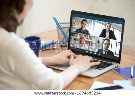 Diverse people take part in group video call pc screen cam app view over woman shoulder, seated at desk. Solve business issues distantly during coronavirus pandemic outbreak, videoconferencing concept #1694685214
