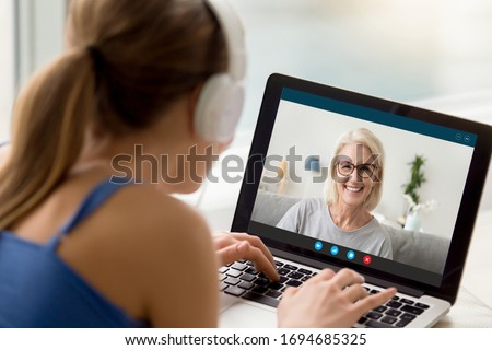 View over shoulder of adult daughter talks by video call with 50s mum. Pc screen view smiling elderly grandmother enjoy virtual chat videoconference with grown up granddaughter. New tech usage concept #1694685325