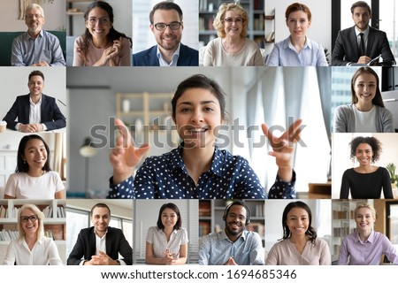 Webcam laptop screen view many faces of diverse people involved in group videoconference on-line meeting lead by indian businesswoman leader, team using video call app work solve common issues concept Royalty-Free Stock Photo #1694685346