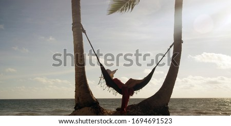 Woman lies in hammock wearing summer dress and hat watching sunset with ocean in the distance #1694691523