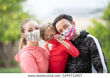 Family members embracing each other, smiling in the camera wearing cloth face masks. Many countries recommend citizens cover their faces during the world coronavirus covid-19 pandemic. #1694712607