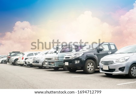 Car parking in large asphalt parking lot with beautiful sunset cloud and sky background. Outdoor parking lot with fresh ozone and green environment of transportation and technology #1694712799