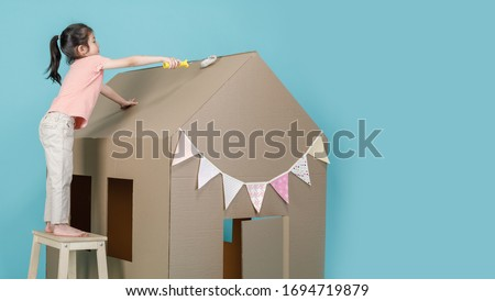Asian little child girl painting her cardboard house isolated on blue long banner with copy space for your text, Creative at home with family concept #1694719879