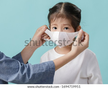 Mom and Asian little child girl is wearing medical face masks to protect themselves from pollution Coronavirus flu virus, New coronavirus 2019-nCoV from China, Empty space isolated on blue background #1694719951