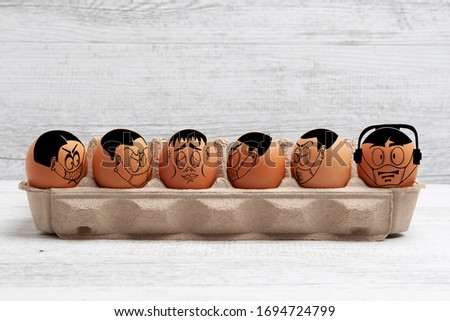 Self isolation and social distancing during Easter concept depicted with cartoon faces drawn on easter eggs with copy space