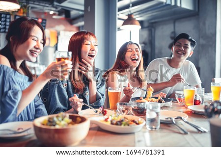 happy young group dining and drinking beer at restaurant #1694781391