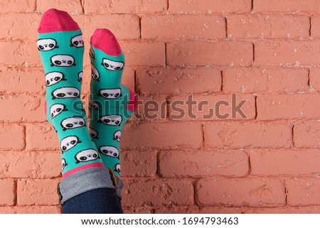 legs in turquoise socks with a picture of panda faces, leaning on a brick wall, grow up, concept, copy space