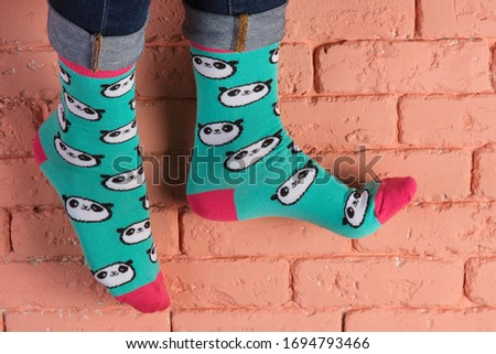 female legs in turquoise socks with a picture of panda faces, as if walking, brick wall background, concept, copy space