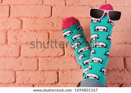 female legs in turquoise socks with a picture of panda faces, stick up, leaning on a brick wall, sunglasses on the leg, concept, copy space