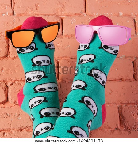 two legs in turquoise socks with a picture of panda faces, stick up, leaning on a brick wall, on the legs are two colored sunglasses, concept, close-up