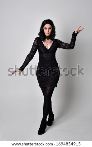 Portrait of a goth girl with dark hair wearing black and plaid skirt with boots. Full length standing pose with back to the camera on a studio background.