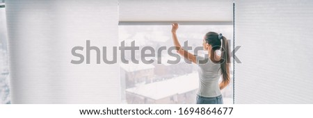 Home lifestyle woman staying in opening blinds shades window treatement cellular honeycomb pleated paper curtains banner background. Royalty-Free Stock Photo #1694864677