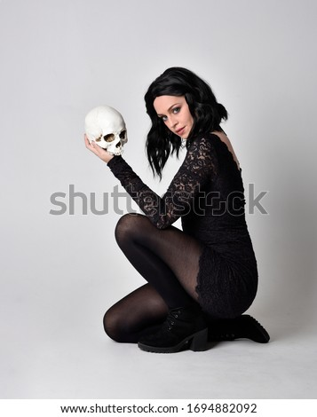 Portrait of a goth girl with dark hair wearing black dress and boots. Full length sitting pose on a studio background