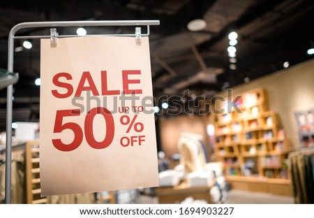 Discount percentage sign display in  fashion department store during sale season period. Sale tag of offering special promotion hanging in shopping mall, Blurred department store background.