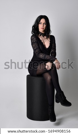 Portrait of a goth girl with dark hair wearing black dress and boots. Full length sitting pose on a studio background.
