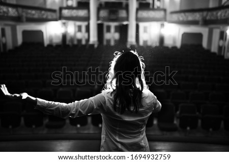 Entertainer performing on a stage in a empty theater,concert hall without fans.No audience.COVID-19 canceled show.Opera house without spectators.Playing to empty seats.Actor/singer entertaining no one #1694932759