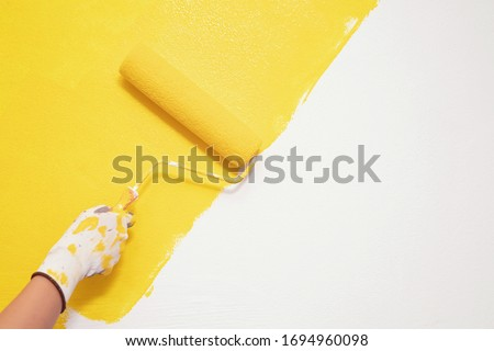Roller Brush Painting, Worker painting on surface wall  Painting apartment, renovating with yellow color  paint. Leave empty copy space white to write descriptive text beside. #1694960098