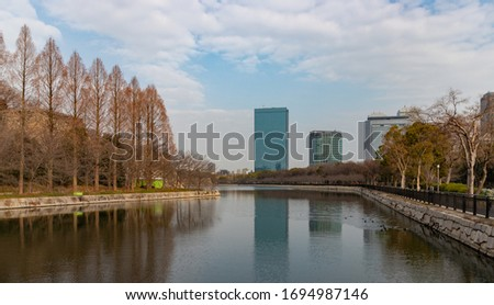 A picture of some buildings of the Osaka Business Park reflected on the moat around the Osaka Castle.
