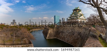 A panorama picture of the Osaka Castle overlooking the Osaka Castle Park and its moat.