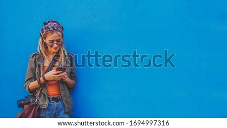 Young girl standing by the blue background holding a smartphone - A hipster stylish girly smiling and checking out social media  Royalty-Free Stock Photo #1694997316