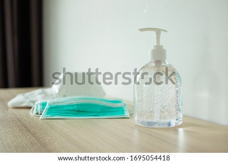Medical face mask with alcohol sanitizer gel hand wash on wood table for covid-19 Coronavirus prevention concept #1695054418