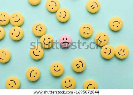One pink pill with drawn sad face among happy ones on color background
