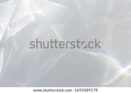 Blurred water texture overlay effect for photo and mockups. Organic drop diagonal shadow caustic effect with rainbow refraction of light on a white wall. Shadows for natural light effects #1695089578