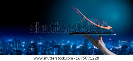 The coronavirus(covid-19) to sinks the global stock exchanges concept.hand holding an empty digital tablet with sinks the global stock exchanges,Corporate representing collapse of the stock market. #1695091228