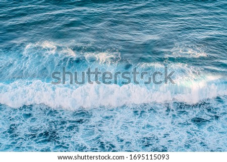 Aerial shot of powerful ocean waves in Bali. Waves break on the shore. Texture of the water surface near the shore above the coral reef. Azure sea natural background. #1695115093