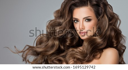 Beautiful model girl with long wavy and shiny hair . Brunette woman with curly hairstyle Royalty-Free Stock Photo #1695129742
