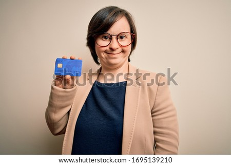 Young down syndrome business woman holding credit card as customer payment with a happy face standing and smiling with a confident smile showing teeth