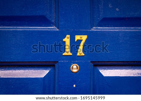 House number 17 on a blue wooden front door with peephole