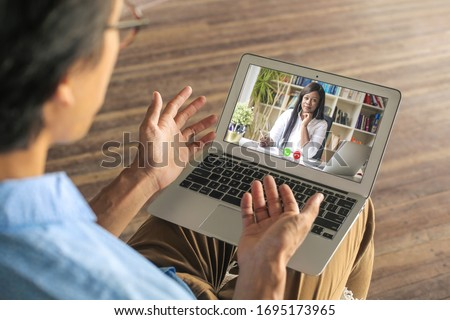 Man video calling his psychologist to have a vistual session while in quarantine during the coronavirus #1695173965