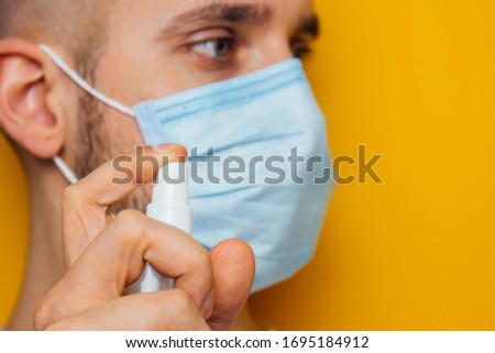 Portrait of a young guy in a mask on a yellow background. Disinfects hands with an antiseptic. Sprays the pest control. The concept of coronavirus. Protection against germs and viruses
