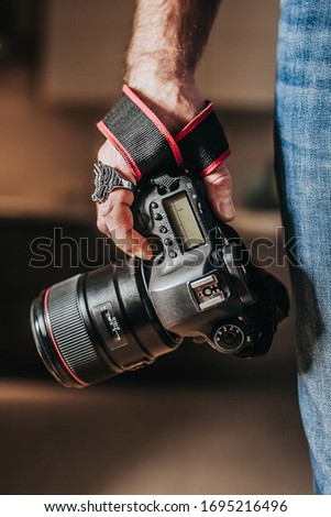 Heavy professional SLR camera with 85 mm portrait telephoto lens - expensive premium photo equipment in the photographer's hand