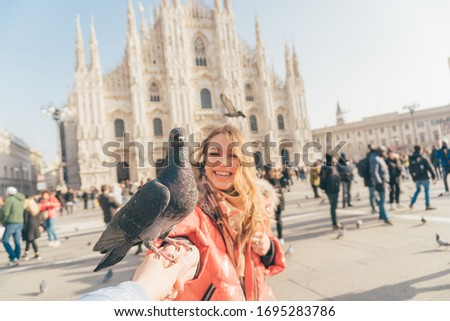 POV image of two girls best friends holding hands and making picture in the square of Milan Cathedral  (duomo di Milano) with dove sitting between them