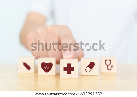 Wood block with icon healthcare medical, Insurance for your health concept Royalty-Free Stock Photo #1695291352