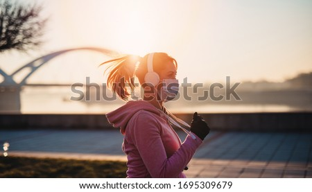 Beautiful young and fit woman in good shape running and jogging alone on city bridge street. She wearing protective face mask to protect herself from virus or allergy infection. Sunset in background. #1695309679