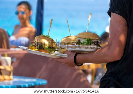 Hand of waiter from restaurant with a terrace on the beach with a view of the turquoise sea carries heavy plates with hamburgers for guests. #1695341416