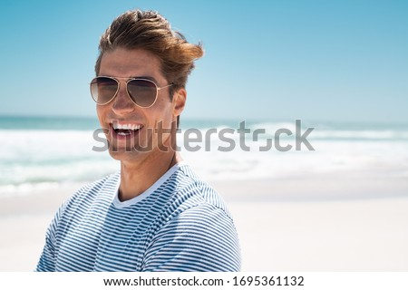 Portrait of handsome young man wearing sunglasses and looking at camera. Portrait of joyful man enjoying summer holiday at beach. Young casual man in shades with big grin and copy space. Royalty-Free Stock Photo #1695361132