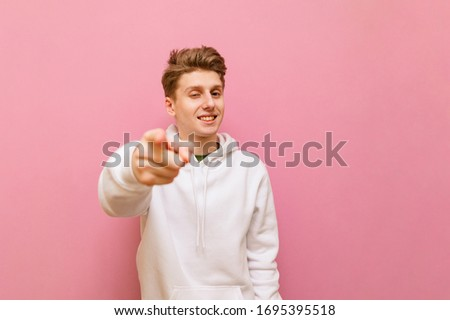 Portrait of a cheerful guy in white casual clothes on a pink background, looks and shows a finger to the camera with a smile on his face. Happy young man is pointing his finger at you. Copy space #1695395518