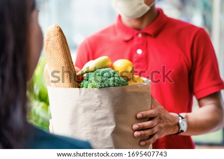 Asian deliver man wearing face mask in red uniform handling bag of food, fruit, vegetable give to female costumer in front of the house. Postman and express grocery delivery service during covid19. #1695407743