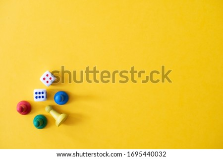 Chess pieces, game chips, Lotto barrels, draughts and playing cubes laid on a yellow background: entertainment, games at home for the whole family, the concept of table games. Board game. Board games #1695440032