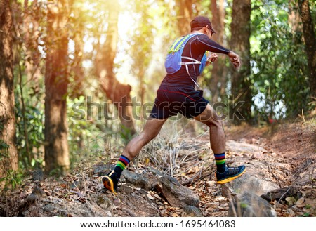 A man Runner of Trail and athlete's feet wearing sports shoes for trail running in the forest Royalty-Free Stock Photo #1695464083