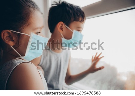 Cute Children Boy and Girl in medical Mask stay Home on Quarantine. Children play Home. Entertainment for the Children during quarantine. Self isolation. Children are looking out the  window.     #1695478588