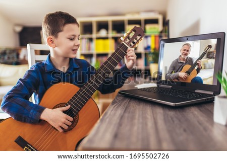 Focused boy playing acoustic guitar and watching online course on laptop while practicing at home. Online training, online classes. #1695502726