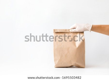 Сoncept of safe home delivery in a pandemic. Coronavirus 2019-nCov Protection. Courier  Paper bag hand in medical glove.Copy space . #1695503482
