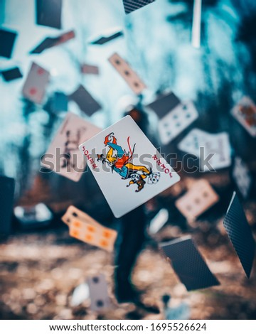 Man Throwing Cards With Joker Showing