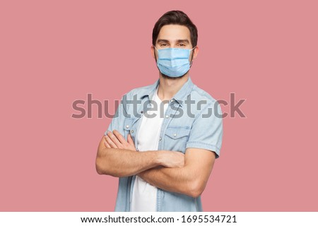 Portrait of handsome young man with surgical medical mask in blue casual style shirt standing, raised arms and looking at camera with smile. indoor studio shot, isolated on pink background. #1695534721