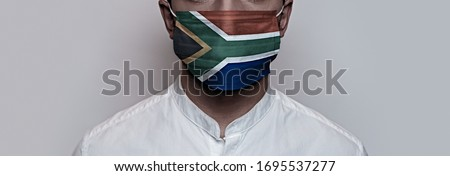 Corona virus pandemic. Concept of Corona virus quarantine, Covid-19. The male face is covered with a protective medical mask, painted in South Africa flag colors Royalty-Free Stock Photo #1695537277